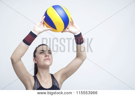 Sport Concepts And Ideas. Professional Female Volleyball Athlete Serves The Ball. Against White
