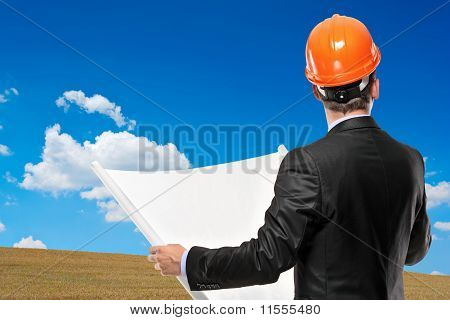 Architect Holding A Blueprint With A Meadow In The Background