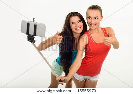 Pretty young girl-friends making selfie with fingers-up.