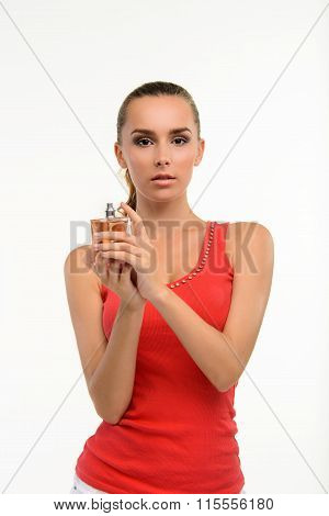 Sensual young woman holding perfume bottle.
