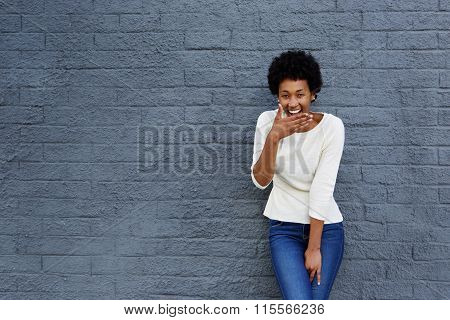 Happy African Woman Covering Her Mouth And Laughing