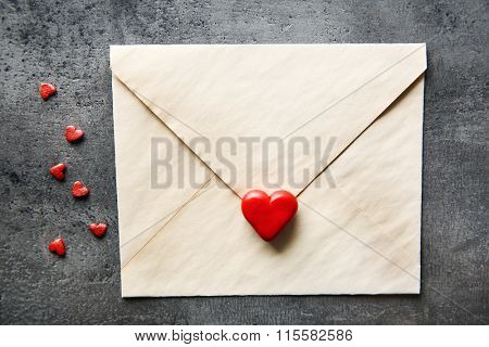 Blank present envelope with small hearts and red rose on grey textured background