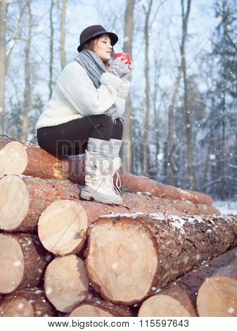 Beautiful young  thoughtful woman holding hot drink wearing knitted scarf and fedora hat covered with snow flakes. Sitting on pile of pine logs. Snowing winter fashion concept.