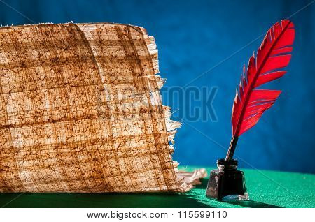 Red quill pen and a papyrus sheet on a green table and with a blue background poster