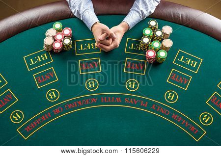 Closeup of poker player with chips at green casino table