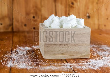 Sugar Cubes in Square Shaped Bowl with Unrefined Sugar spill over in Wooden Background