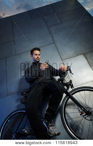 Sporty man waiting by wall, leaning against bicycle, texting on mobilephone. Photographed from below.