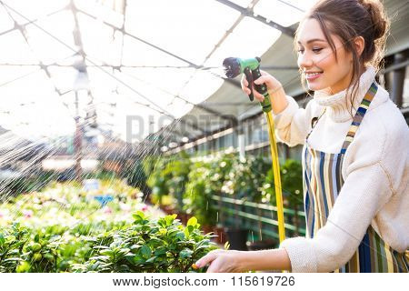 Happy pretty woman gardener in uniform watering plants with garden hose in greenhouse