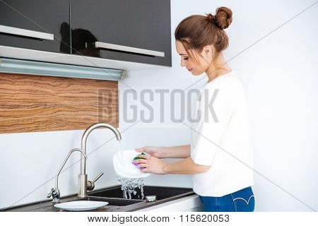 Cute lovely young woman standing and washing dishes at home