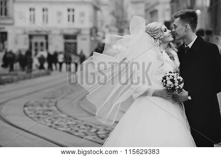 Happy Couple Of Newlywed Valentynes Posing And Kissing In Old European Street B&w