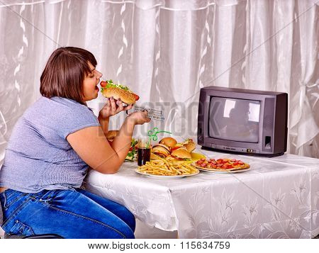 Overweight woman eating fast food and watching TV. Concept junk.