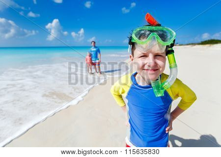 Boy and his family with snorkeling equipment enjoying beach vacation