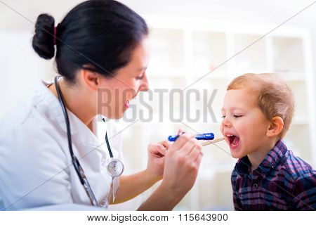 Medical doctor with child in office. Pediatrician examining little boy's throat with tongue depresso