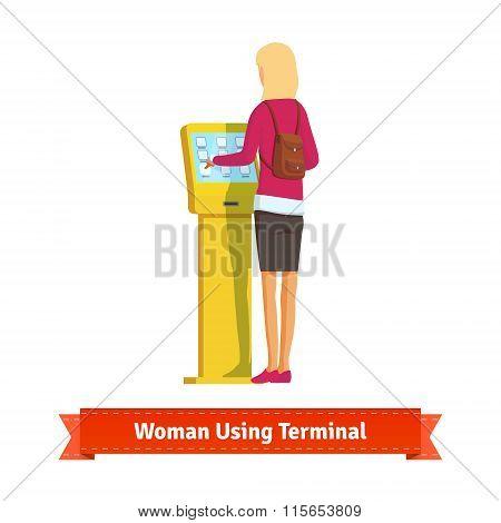 Woman using electronic self-service terminal