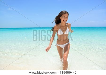 Cheerful young woman running on beach having fun laughing during summer holidays travel. Exhilarated female is in white bikini smiling. Beautiful tourist is enjoying vacation on beach.