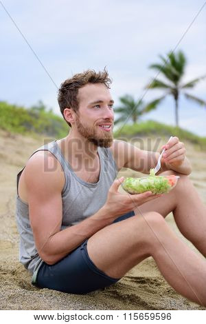 Fitness man eating healthy salad meal at workout. Handsome young muscular male adult sitting on the beach after running workout for lunch break with fresh prepared to go vegan raw vegetables food.
