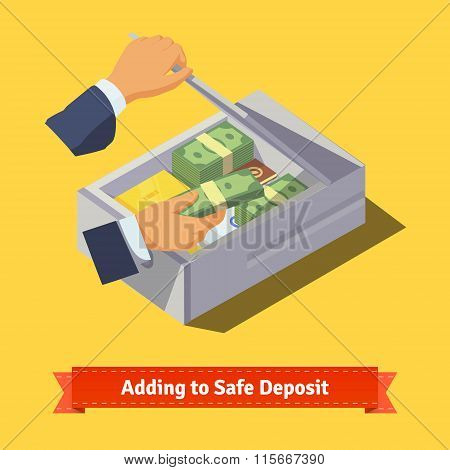 Hands putting money and valuables to a deposit box