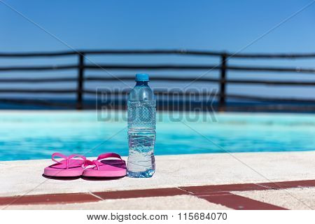 Plastic Bottle With Pure Water And Slippers Near Swimming Pool