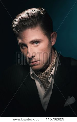 Stylish Vintage Fashion Dandy Young Man With Scarf In Suit. Against Dark Blue Wall.