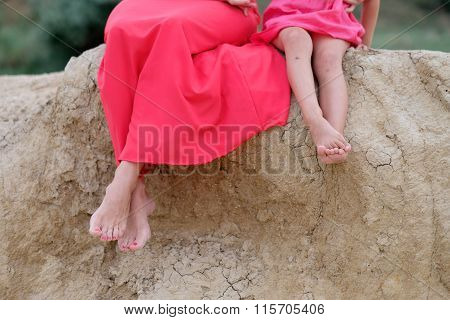 Feet Of The Young Mother With A Baby In Nature