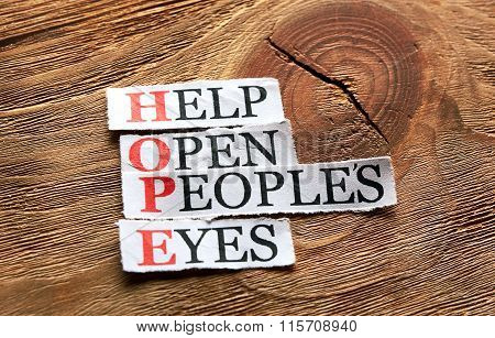 hope acronym - Help Open Peoples Eyes words on cut paper on wood background poster