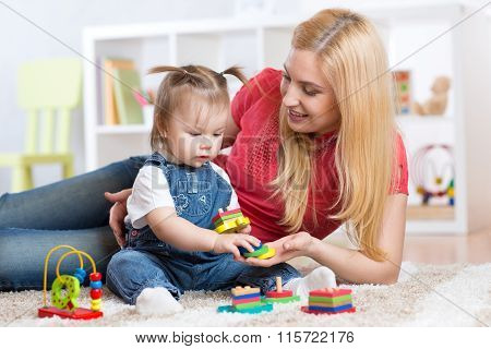 Mother teaches her child to distinguish shape and colur plaing with toys.