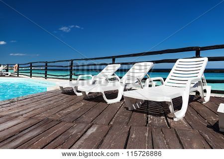 Luxury Sunbeds On Wooden Floor Near Swimming Pool