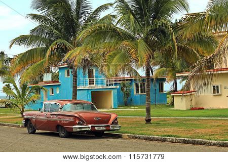 HAVANA, CUBA - JULY 6, 2015: American red car parked under palms near the Tarara  beach.