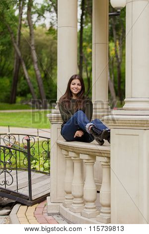 The beautiful girl on an arbour handrail