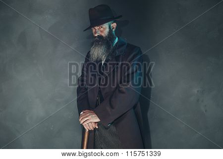 Mysterious Vintage Beard Man In 1900 Style Fashion With Cane Against Grey Wall.