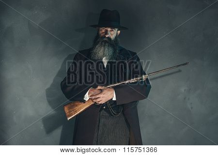 Spooky Vintage Beard Man With Rifle In 1900 Style Fashion Against Grey Wall.
