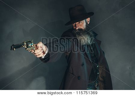 Gun Shooting Vintage Crook With Long Beard In 1900 Style Clothing Against Grey Wall.