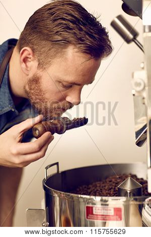 Business owner smelling freshly roasted coffee beans for aromati