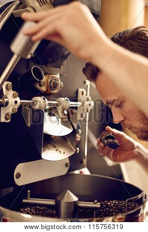 Man operating a modern coffee roasting machine and smelling the