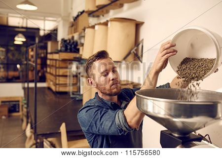 Male entrepreneur in his coffee roastery and distribution space preparing a new batch of roasted beans, by pouring a container full of raw beans into a modern machine poster