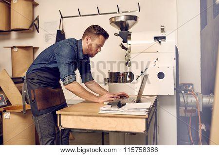 Modern coffee roaster using his laptop alongside a modern roasti