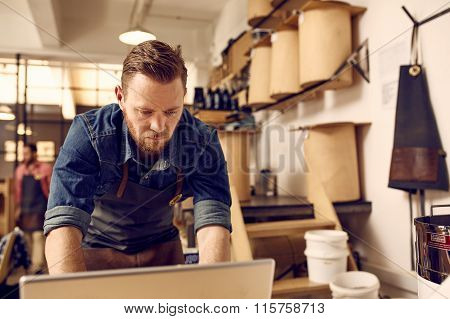 Hipster business owner working on laptop in his modern work