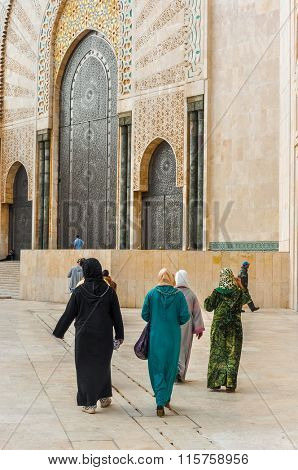 CASABLANCA, MOROCCO, APRIL 2, 2015: Local women in traditional attire walk on the outside grounds of Hassan II Mosque or Grande Mosquee Hassan II