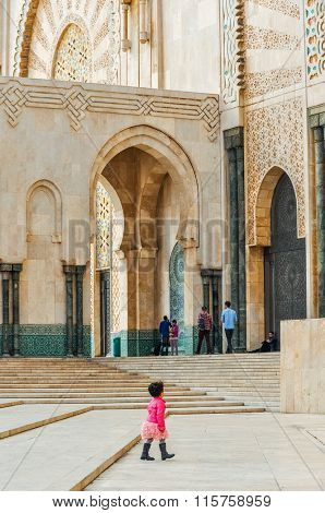 CASABLANCA, MOROCCO, APRIL 2, 2015: Local little girl walks on the outside grounds of Hassan II Mosque or Grande Mosquee Hassan II