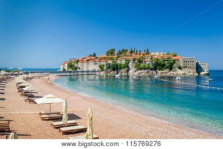 Sveti Stefan luxury sand beach with chaise-longue chairs and umbrellas