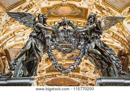 Angel statues holding laurel wreaths. Christian Church decoration.