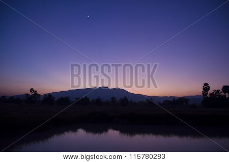 Blue dusk Mountains reflected in lake