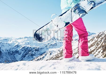 Back view close up of female snowboarder wearing blue jacket, grey gloves and pink pants standing with snowboard in one hand and enjoying sunny alpine mountain landscape - snowboarding concept