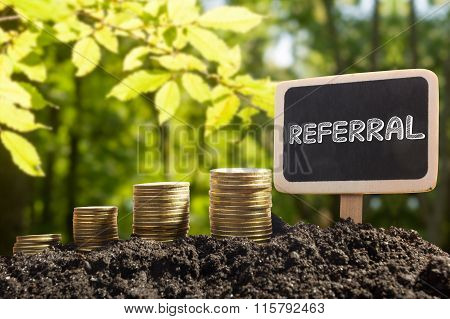 Referral - Financial opportunity concept. Golden coins in soil Chalkboard on blurred urban backgroun
