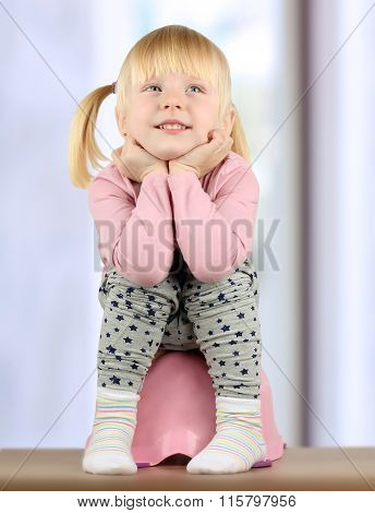 Small  Smily Girl Sits  On A Potty