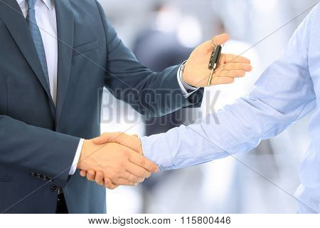 Car Salesman Handing Over The Keys For A New Car To A Young Businessman . Handshake Between Two Busi