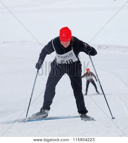 Smiling Cross Country Skiing Woman In A Steep Uphill Slope