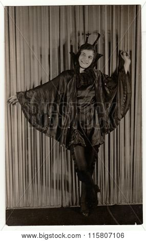 Vintage portrait photo shows young girl in a retro carnival costum (devil costum).