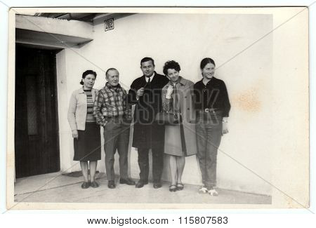Photo shows a group of people in front of house, 1970s.