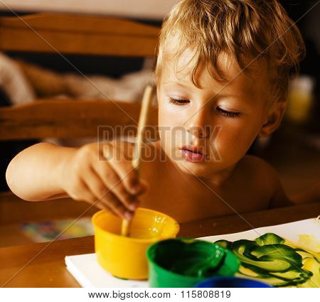 portrait of little boy painting at home interior close up